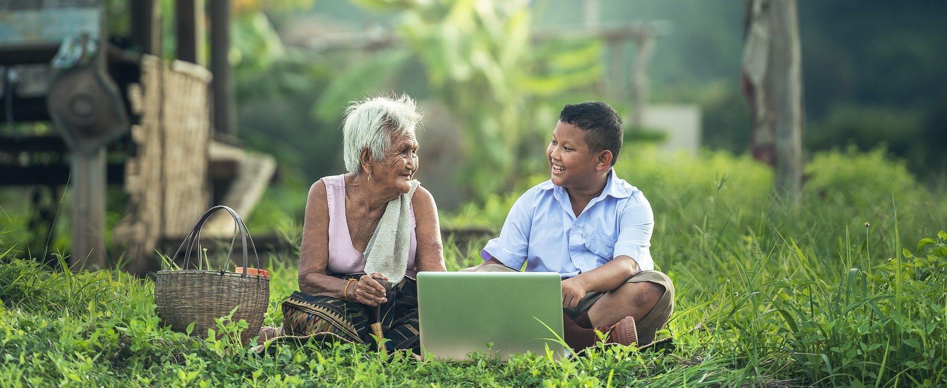 Großmutter und Sohn vor Notebook